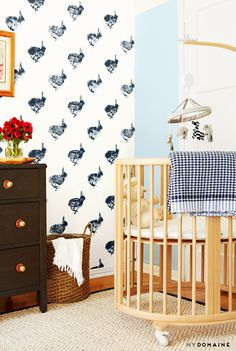 Light wood crib with blue blanket, mobile, poppies, blue bunny wallpaper and dark dresser