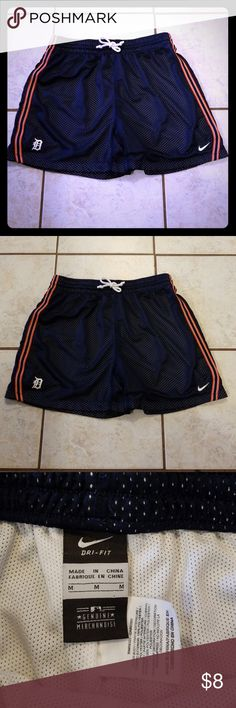 Nike Dri-Fit Detroit Tigers Draw String Shorts Nice Nike Dri-fit shorts featuring the Detroit Tigers baseball team. Dark blue with orange and white detail. There is a tear in the interior fabric lining inside the right leg, see last photo. Other than that they are in good condition. Priced with this in mind. White draw string. 100% polyester. Great for summer! Nike Shorts