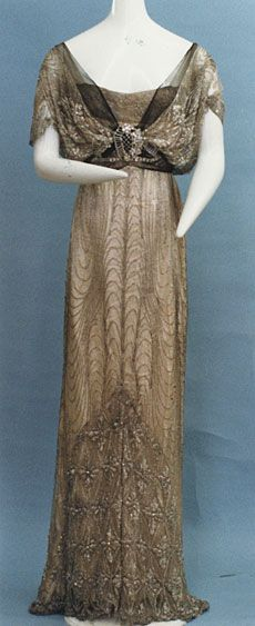 "Evening dress, ca. 1912. Beige silk tulle embroidered with beads and rhinestones; black silk tulle and silver lace decoration; silk satin underdress. I have seen this attributed to Poiret on many sites, but this photo is from the Kyoto Costume Institute, which credits it to ""Doeillet"" (I think they mean ""Doeuillet"")."