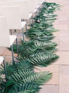 a palm leaf lined wedidng aisle for a modern wedding ceremony space