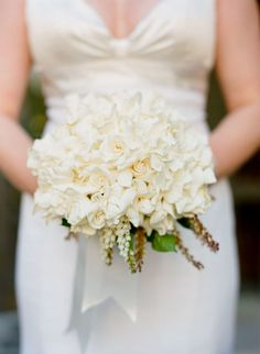All white bridal bouquet with hydrangea and ivory garden roses. Bride wears an elegant minimalist V-neck charmeuse wedding gown by Manhattan bridal fashion designer Selia Yang.