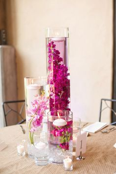 """Trio of cylinders (20"""", 12"""", 8"""") with submerged flowers: one with bright coral snapdragons, one with light coral spray roses, and one with a peachy pink garden rose. Surrounded by stemmed votives with floating candles in turquoise water and silver mercury glass votives.  www.stemfloral.com  I  www.michelleboydphotography.com"""