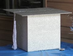 Graduation Cap Card Holder Made from cardboard box, cardboard for the top, and the tassel was made from twine. Box was wrapped with silver glitter wrapping paper. #graduationcap #card #holder #cardholder #graduation #party #graduationparty