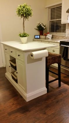 DIY farmhouse style kitchen island with seating for a small kitchen space. Buffet was converted into this island with a little chalk paint, top, trim, and a paper towel holder.
