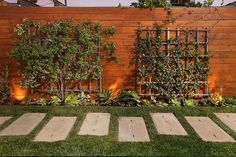 This warm wood privacy fence design features attached lattice mounted greenery.