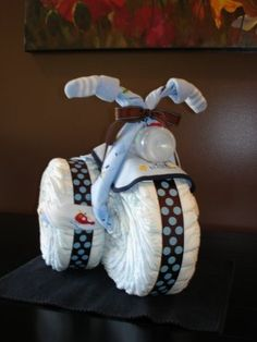 aby shower gift made out of diapers, ribbon, bottle, bib, onesie, and socks