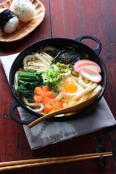 udon noodles, dashi soup, soy sauce, mirin, salt, spinach, carrot, enoki mushrooms, wakame seaweed, kamaboko (Japanese fish cake), egg, long green onion, shichimi spice