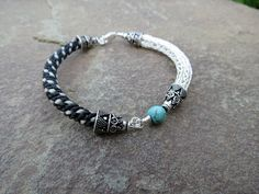Custom horse hair bracelet using tail hair from a client's 3 horses.  Trimmed with sterling silver end caps and clasp.  Viking knit section hand crafted from 24g sterling silver wire.  African turquoise bead.  www.seeingthingsvisualarts.com