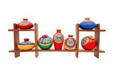 Frame in Sheesham wood. With set of seven warli painted miniature pots. Will add colour and life to your walls. A classy yet ethnic piece of art.