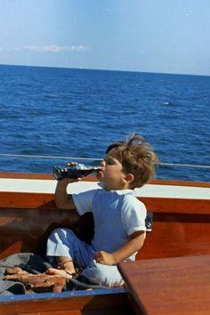 John F. Kennedy Jr. enjoying some Coca-Cola, aboard his fathers yacht, c. 1963