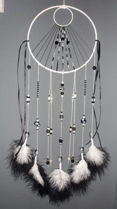 Superbe attrape-rêves, thème étoiles, à base de perles de qualité, de ficelle et de plumes. Les 2 cercles sont composés de plusieurs tours de fil de fer, le tout recouvert de ficelle de coton...