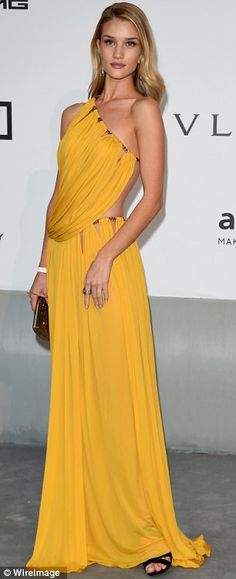 Grecian goddess: British model Rosie Huntington-Whitely looked like a Grecian goddess wearing a flowing yellow gown featuring cut-out detail...