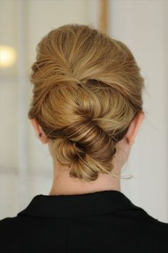Love this hairstyle and it is super easy to do, especially day after washing. Pull back front and hair at crown (no part) after spraying (w/ P. Mitch. finishing spray.) Twist over and bobby pin it like a mini French twist. Then grab hair at nape and twist the entire length. Grab at halfway point and twist/curl up to form a little bun then pin like crazy and spray. Watch video for