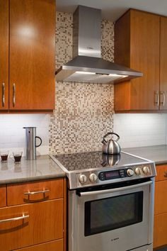 The kitchen backsplash is a combination of limestone subway tiles and a mixed limestone mosaic band behind the vent hood.