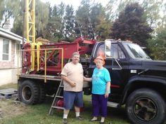 Mom and Ope in front of Dad's well drilling machine that Ope redid.