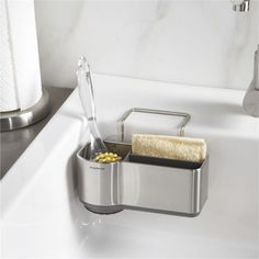 Sleek design from simplehuman unclutters the sink.  Rust-proof stainless steel caddy has plastic dividers to organize sponges and scrubbers; pop-out silicone brush holder extends for longer brushes.  Affixes to sink with suction cups and a wire ledge hanger. Stainless steel, plastic and siliconeHand washMade in China.