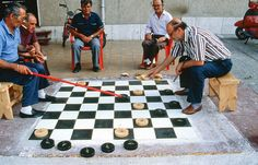 This guys play checkers in a big way.  Men playing checkers on a giant board in Agropoli, Italy.