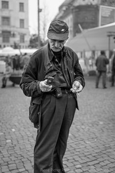 An old man texting. With his trousers high on the waist, he looks like a trunk, asan old tree in the middle of the fair. Texting, Old Men, Street Photography, Trunks, Trousers, Hipster, Style, Text Messages, Drift Wood