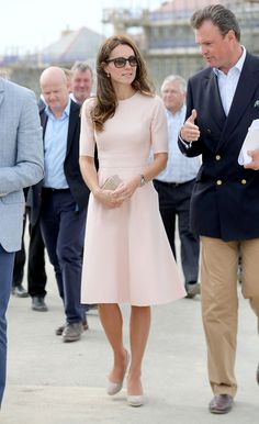 The Duchess of Cambridge in a blush pink fit-and-flare frock from Lela Rose, box clutch, suede espadrille wedges, Cartier's Ballon Bleu watch and Ray-Ban wayfarers.