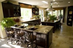 This eat-in kitchen has a series of big, seamless windows that let in lots of natural light. The L-shaped countertop extends into an eat-in bar with seating for three.