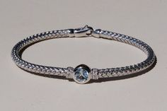 Sterling Silver Woven Cable Bracelet with a Round Blue Topaz Center Stone and Diamond Side Stones from J. Schrecker Jewelry. Visit us at our website or at www.facebook.com/JSchreckerJewelry.