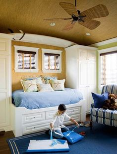 """Seaside Bedroom    Just a two-minute walk from the beach, this boy's bedroom boasts a """"surfer dude"""" attitude by the surfboard hanging above the bed. The colors of sand and sea abound, from the beige woven rattan wall covering to the ocean-blue area rug below. Starfish pillows add seaworthy style. A distressed-look walnut floor helps hide the sand tracked in during the summer. The built-in bed includes drawers for stowing clothes and toys."""