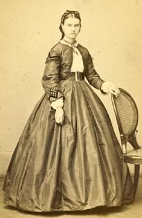 1861-1865 Smart looking skirt, blouse and jacket with medium sleeves and sleeve cap, both with braid trim.  Flattering outfit with wide belt.