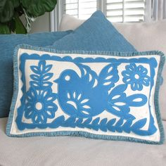 """Our Mexican Bird pillow is inspired by the traditional paper garlands of Mexico.  Our design is a hand-cut felt applique in soft blue, that is offset beautifully on a creamy heather background.  Appliques are accented with contrasting top-stitch thread and sophisticated wool felt trim.  Feather/down fill is included.  Dimensions:  20"""" X 12"""" Materials:  100% wool felt, cotton brush fringe Fill:  feather/down blend   ...MADE BY CHEEKY MONKEY HOME"""