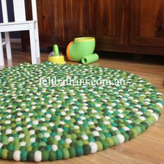Green Felt Ball Rug. This  green felt ball rug is hand sewn together and can be used on both sides.  These stunning rugs are perfect for any room in the house. With the flair and creativity of the design these heavy duty rugs would last a lifetime and are sure to make a statement.  Each felt ball is 100% New Zealand soft wool, is felted and then hand stitched together.