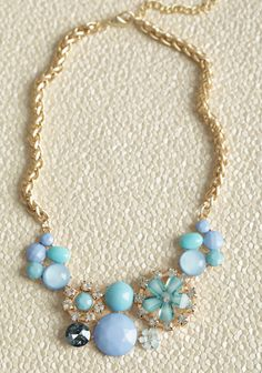 Floral Radiance Necklace 22.99 at shopruche.com. This charming gold-toned statement necklace features a medley of jewels and stones in hues of aqua and periwinkle. Perfected with classic rhinestones, floral pendants, and a hint of glitter.15