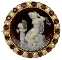 """Tiffany & Co. Red Enameled Venus and Cupid Cameo Diamond and Ruby Pin An intricately detailed turn of the century Tiffany & Co. Venus and Cupid Cameo. The cameo is made with red and white enameling, set on 18k yellow gold, surrounded by Old European cut diamonds and rubies.??Signed on the back """"Venus & Cupid""""?""""Tiffany & Co"""" Year Made: Victorian"""