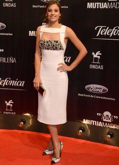 Michelle Jenner con un vestido midi en blanco con original escote y detalle joya de Bulberry.