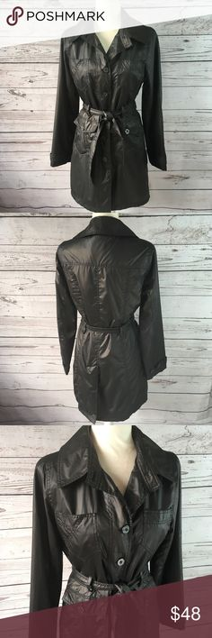 """Bebe Black fabric lightweight trench coat Bebe Black fabric lightweight trench coat. Very subtle bronze sheen to coat doesn't show up in photographs very well but you can see it a little if you enlarge the pics. Excellent pre-loved condition. No stains or tears. Washable polyurethane with polyester lining. Bebe logo buttons on front, sleeves, and 2 front tab pockets. To open pockets on test. All measurements taken with item laying flat and our approximate  •Armpit to armpit• 19.5"""" •Waist•17""""…"""