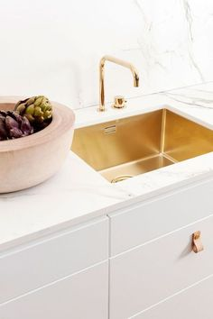A beautifully stylish look for a kitchen … brass sink and tapwear, white cabinets with leather tab pulls and a Dekton (in aura) countertop and splash-back   by Ballingslov ~ x debra  Dust Jacket on B