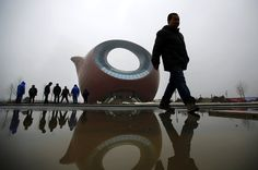 Workers stand next to a building shaped like a clay teapot in Wuxi, Jiangsu province, China