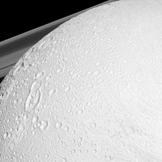 Northern Reaches: The Cassini spacecraft watches over the northern latitudes of Saturn's geologically active moon Enceladus while the planet's rings peek through in the distance in this snapshot.