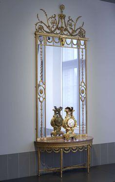 John Linnell (II) | Pier table and mirror, John Linnell (II), c. 1775 | Halfronde wandtafel met spiegel van verguld hout, rustend op vier conische gecanneleerde versierde poten. Het kruis is van achteren recht en van voren driemaal concaaf gebogen. Regel met vlechtband en rozetten; onderaan met tien halfcirkelvormige rozetten, waaronder kelksnoeren. Paars scagliola blad. De driedelige spiegel toont aan weerszijden kelkranken, in het midden verbonden door vlechtwerk met rozet. Bovenaan een…
