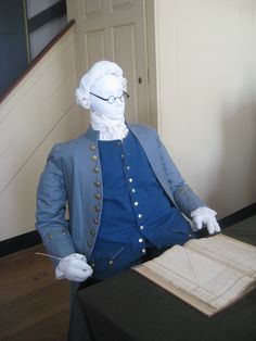 Clerk, c. 1770s Blue cloth suit, with wool waistcoat and breeches, adapted from various period sources; cotton stockings, silk neckcloth, leather shoes, reproduction spectacles. A working man would dress less elegantly than a businessman, but certainly as well as he could afford; for a clerk in the Potts' employ, another version of the 18th century suit is shown. Here, a blue wool waistcoat and breeches are the matching components of the suit; a blue cloth coat completes the outfit.