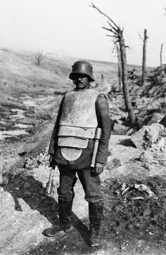 "A German member of a ""Trench Attack Squad"" poses in steel body armor and two stick grenades. The armor, capable of stopping a pistol round but only superficially helpful against rifle fire, also helped protecting against bayonet and other edged weapons thrusts. The additional weight though fatigued the wearer quickly and defeated any tactical advantage he might have wearing it."