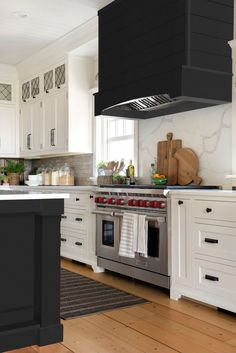 This black and white kitchen has modern farmhouse accents. The white kitchen countertops and white cabinets brighten up the room and the black kitchen hood and black island give it a modern feel. #kitchen #farmhouse #whitekitchen Home Decor Kitchen, Kitchen Interior, New Kitchen, Kitchen Ideas, Island Kitchen, Kitchen Paint, Two Toned Kitchen, Kitchen Hoods, Modern Farmhouse Kitchens