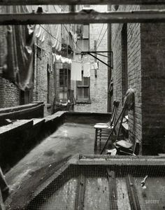 """Rear Window: 1936   June 1936. """"View out of rear window tenement dwelling of Mr. and Mrs. Jacob Solomon, 133 Avenue D, New York City. The Solomon family are all on the accepted list for resettlement at Hightstown, New Jersey."""" Medium-format nitrate negative  by Dorothea Lange for the Resettlement Administration."""