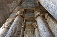 """[EGYPT 29521] 'Outer hypostyle hall of Hathor Temple at Dendera.'  The columns in the outer hypostyle hall (or pronaos) of the Hathor Temple at Dendera are crowned by four-sided capitals carved with the face of the cow-eared goddess. The faces symbolize the four cardinal points of the universe and stress the universal character of the sky goddess Hathor, who was also called """"Lady with the four Faces"""". Here we are looking towards the eastern end of the hall. The ceiling has recently been…"""