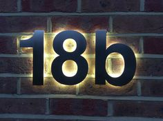 Our latest design solution for a LED back-lit house number based on the Helvetica typeface perfectly installed by a discerning customer. Bespoke design service - contact Housenumbers Limited directly at http://www.housenumbers.co.uk/illuminated-house-numbers-8-c.asp