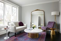 """Laura's favorite room, by far, is the living room. She says, """"The living room feels very feminine but modern and the bright colors really get people's attention when they first walk into the house."""" Just look at that deeply-colored <a href=""""http://www.luluandgeorgia.com/rugs/all-rugs/mirabelle-rug-pink-95684?___SID=U"""" target=""""_blank"""">rug</a> and royal purple <a href=""""http://www.anthropologie.com/anthro/product/29292364.jsp?cm_vc=SEARCH_RESULTS#"""" target=""""_blank"""">chair</a>! We don't care if…"""
