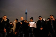 People raise pens and signs during a vigil to pay tribute to the victims of a shooting by gunmen at the offices of weekly satirical magazine Charlie Hebdo in Paris, at Trafalgar Square in London, Jan. 7, 2015.