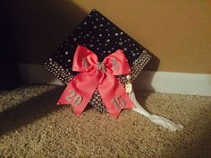 Cute graduation cap with rhinestones, pearls, as well as, a pink bow.