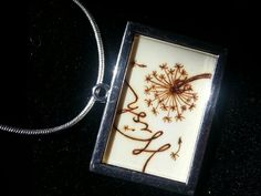 """Old ivory piano key trimmed to slide into a photo charm. I love dandelion""""wishes""""! (Wood burned image)"""