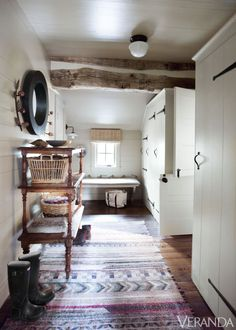 Hand-hewn logs and antique accents create a timeless look in the mudroom.  Pine étagère, Henhouse Antiques; mirror, English Accent Antiques; ceiling fixture, Urban Archaeology; rug, Keivan Woven Arts; walls in Bleeker Beige, Benjamin Moore.