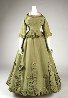 Green silk dress with fringe, satin-edged ruffles, and satin ribbon and bow trim, American, 1863-66.