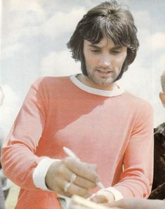 July 1971. Manchester United and Northern Ireland winger George Best signing autographs during a club photo shoot.
